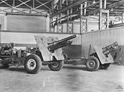 Two artillery guns mounted on wheeled gun carriages photographed inside of a building. The weapons have a large plate mounted about half way down the length of their barrels.