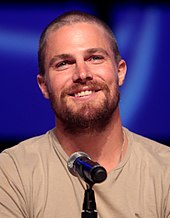 A photograph of Stephen Amell speaking at a convention behind a microphone