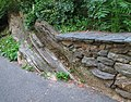 Stone wall runs into rock outcrop, Isham Park.jpg