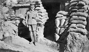 Soldier in peaked cap and puttees outside a sandbagged entrance.
