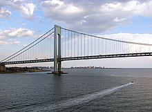 View of the Verrazzano-Narrows Bridge looking south from Upper New York Bay. The neighborhood of Coney Island in Brooklyn can be seen in the distance.