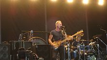 A bassist/singer, Sting, is shown at a performance. A number of speaker cabinets are shown onstage.