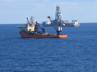 Petroleum reservoir - The drillship Discoverer Enterprise is shown in the background, at work during exploratory phase of a new offshore field. The Offshore Support Vessel Toisa Perseus is shown in the foreground, illustrating part of the complex logistics of offshore oil and gas exploration and production.