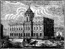 A neoclassical building seen from an angle. It has two storeys and a dome on a high drum. A horse and cart pass in front of it and to the right of the hall is a covered wagon