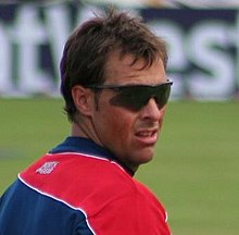 A man wearing sunglasses and navy blue and red English cricket T-shirt looks across over his shoulder at a sports ground. A sponsorship board is visible in the background.