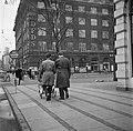 Twee mannen achter een kinderwagen in een winkelstraat, Bestanddeelnr 252-8843.jpg