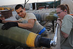U.S. Air Force Airman 1st Class Anthony Anderson (left) holds a bomb in place as Staff Sgt. Misty Lowe tightens its super bolt at Kandahar Airfield, Afghanistan, on Aug. 23, 2010 100823-F-OL185-690.jpg