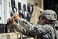 U.S. Army Sgt. Matthew Lei, assigned to the 565th Quartermaster Company, unhooks cargo straps on an M1088 tractor truck at the Indiana National Guard Armory in Scottsburg, Ind 120802-F-HS649-138.jpg