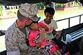 U.S. Marine Corps Col. John Ostrowski, left, the officer in charge of the III Marine Expeditionary Force's humanitarian assistance survey team (HAST), holds a Thai boy after helping him into a vehicle while 111018-M-ZN194-223.jpg