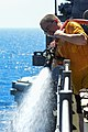 U.S. Navy Operations Specialist 1st Class Thomas Knapp participates in a fresh-water washdown aboard the guided missile cruiser USS Monterey (CG 61) June 22, 2013, in the Persian Gulf 130622-N-QL471-164.jpg