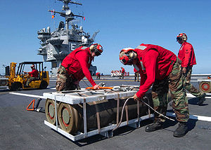 Mark 84 bomb - Sailors remove hoisting sling from a crate containing a pair of Mark 84 bomb bodies. Tailfins and fuzes have not yet been fitted