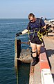 US Navy 041103-F-2760K-001 Interior Communications Electrician 3rd Class James Lester, assigned to Explosive Ordnance Disposal Mobile Unit Eight (EODMU-8), Detachment Eighteen, holds a line attached to submerged divers.jpg