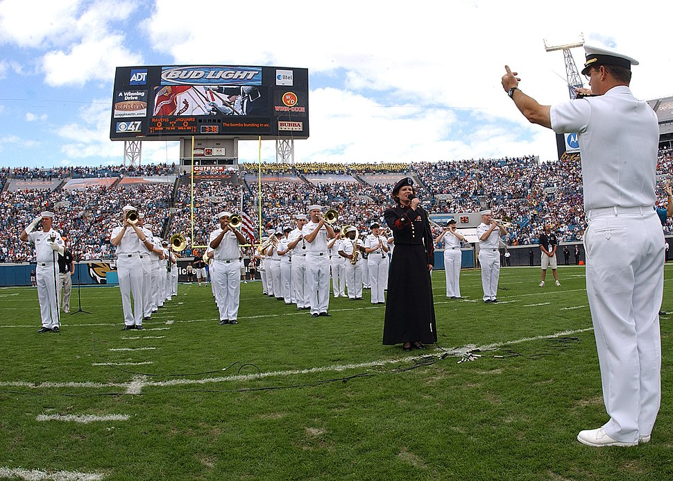US Navy 051113-N-1126D-004 Navy Band Southeast performs the National Anthem as U.S. Army Staff Sgt. Erica Russo sings the anthem at the Jacksonville Jaguars pre-game ceremony