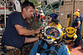 US Navy 070808-N-3093M-020 Chief Navy Diver Scott Maynard of Mobile Diving and Salvage Unit (MDSU) 2 makes final checks on Navy Diver 2nd Class Noah Gotteman's MK-21 diving helmet.jpg
