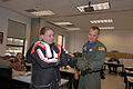 US Navy 080612-N-8102J-113 Aviation Warfare Systems Operator Airman Apprentice Jessica Deaver demonstrates how to properly don an anti-exposure suit with the assistance of Aviation Warfare Systems Operator 1st Class Jeremy Aule.jpg
