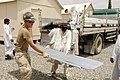 US Navy 080630-N-6477M-432 Builder 2nd Class Ian M. Seiler, assigned to Naval Mobile Construction Battalion (NMCB) 3 Det. 4, works with Afghani nationals to unload a shipment of sheet metal.jpg