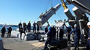 US Navy 081120-N-0000X-001 Members of USS Fitzgerald's (DDG 62) Harpoon handling team carefully lower an all-up-round Harpoon missile into its launch rack on the aft VLS deck during ammunition onload operations