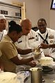 US Navy 101013-N-1938G-016 Yeoman 2nd Class Arica Blake, assigned to Navy Operational Support Center, Atlanta, pipes frosting on a cake with assist.jpg