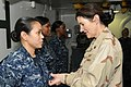 US Navy 101207-N-7571G-077 Rear Adm. Margaret Klein pins an Enlisted Surface Warfare Specialist insignia on Hospital Corpsman 1st Class Jennifer Ga.jpg
