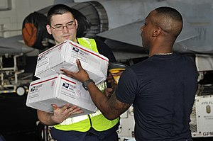 US Navy 111220-N-ZI635-459 Logistics Specialist Seaman Justin McLaurin, right, scans packages as mail arrives aboard the Nimitz-class aircraft carr.jpg