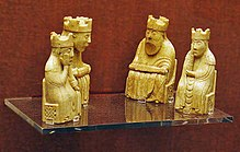 Four gold-coloured chess pieces sit on a glass shelf with a red wall in the background. All four pieces are seated and wear crowns. Two of the pieces are larger and have beards, the other two are female figures.