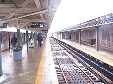 The platform level on a snowy day, on the center island platform. A train is stopped on the left-hand track. On the right is another, empty track, as well as a disused side platform with a white windscreen.