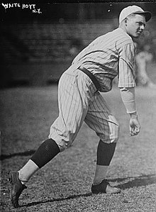 A man wearing a pinstriped baseball uniform stands truned to his left having just thrown a baseball.