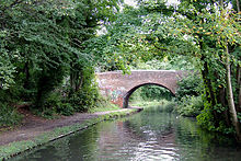 red bricked bridge over a small canal, surrounded in green