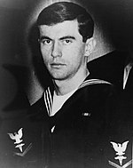 A picture of a man in a United States Navy uniform while looking at the camera with a stern face.