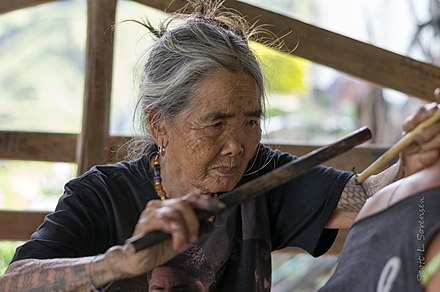 Whang-od, the last mambabatok (traditional Kalinga tattooist) of the Kalinga in the Philippines, performing a traditional batek tattoo. Whang-od tattooing.jpg