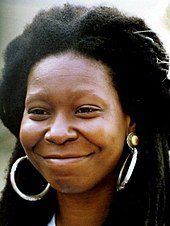 Headshot of Whoopi Goldberg. She has thick black hair and is wearing large hoop earrings.