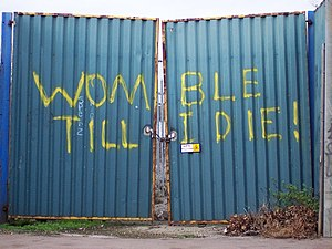 "Relocation of Wimbledon F.C. to Milton Keynes - Graffiti on the locked gates of Wimbledon F.C.'s traditional home ground, Plough Lane, in 2006. The club, nicknamed ""the Wombles"" or ""the Dons"", last played first-team matches there in 1991, and the stadium was demolished in late 2002. Blocks of flats have covered the site since 2008."