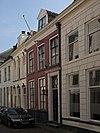 foto van Pand met rechte lijstgevel, voordeuromlijsting met geblokte pilasters en halfrond beëindigde ramen op de verdieping