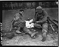 111-SC-248455 - PFC George Cap, from Prior Lake, Minn., and Pvt. James McFarland, of Zanesville, Ohio, both of the 1st Division, U.S. First Army, play cards, as they wait for orders to move out of Vettweiß, Germany.jpg