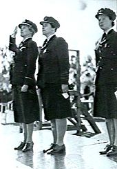 Three women in dark military uniforms standing to attention on a platform
