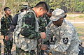 A member of the Royal Thai Army gets help with an American standard-issue Improved Outer Tactical Vest from U.S. Army Pfc. James Phillips, right, during exercise Cobra Gold 13 at an unknown location in Thailand 130212-A-LK473-001.jpg