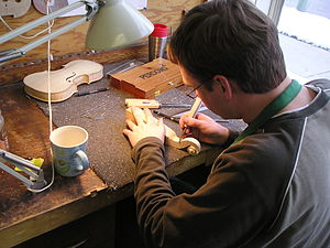 Violin making and maintenance - A new violin scroll being carved.