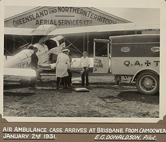 Royal Flying Doctor Service of Australia - One of the original De Havilland DH.50 machines used flown by Qantas, in this case doing ambulance work, delivering a patient at Brisbane in 1931.