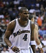 "A man of darker complexion wearing a white uniform, on the jersey of which the word ""WIZARDS"" is printed."