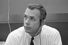 A man in a dress shirt and tie wears a headset