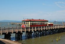 The streetcar passing over a low wooden trestle connected to a dock on the Columbia River