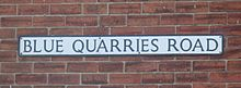 "On a red brick wall, a rectangular sign bears the name ""Blue Quarries Road"" in black, upper case letters on a white background."