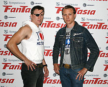 Two men in their mid-20s stand with their hands at their hips and facing the camera. The man on the left, Jason Trost, has short brown hair and wears an eyepatch, a sleeveless hooded sweatshirt, and black jeans. The man on the right, Brandon Trost, also has short brown hair, wears a denim jacket over a gray t-shirt with an unreadable graphic, and blue jeans.