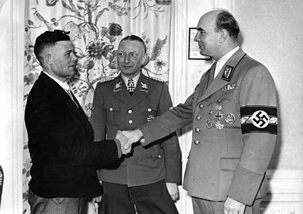 "Arthur Greiser welcoming millionth Volksdeutscher resettled during ""Heim ins Reich"" action from the East Europe to occupied Poland - March 1944 Bundesarchiv Bild 183-J09397, Lodz, Millionster Umsiedler im Wartheland.jpg"