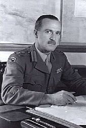 Head-and-shoulders portrait of moustachioed man in military uniform at desk