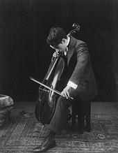 Chaplin, de profil et la tête en bas, assis sur un tabouret, jouant un violoncelle entre ses jambes
