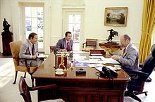 A man sits at his desk, smoking a pipe, while two other men speak to him from the other side of the desk.