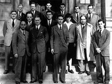A group of people in suits standing in three rows on the steps in front of a stone building.