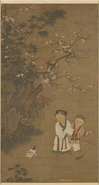 Two young girls play with a toy consisting of a long feather attached to a stick, while a cat watches them. There is a large rock formation and a flowering tree to the left of the girls and the cat.