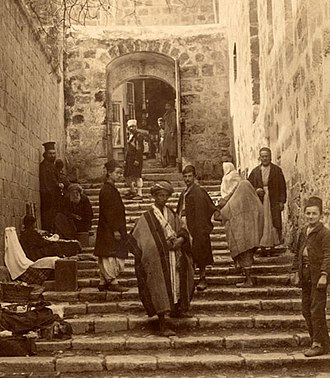 Tourists, pilgrims and locals at one of the two access gates to the Holy Sepulchre courtyard, photo by Bonfils, 1870s Church of the Holy Sepulchre by Felix Bonfils.jpg